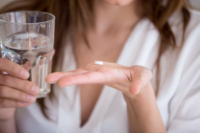 Woman taking antibiotics with water which may influence her gut microbiome