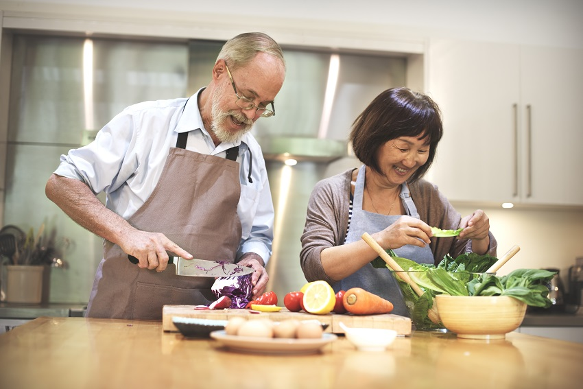 Middle age couple cooking healthy food together in the kitchen for better gut microbiome health