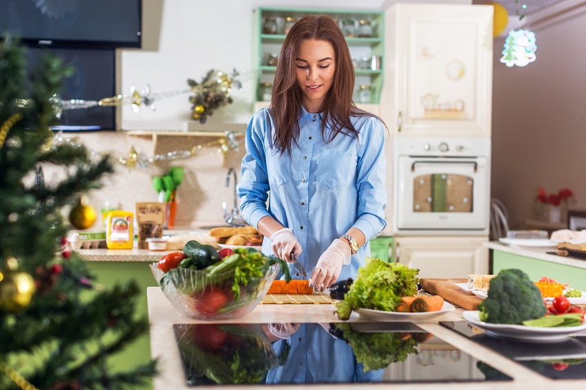 Woman preparing a healthy, festive season dish in the kitchen for better gut microbiome health